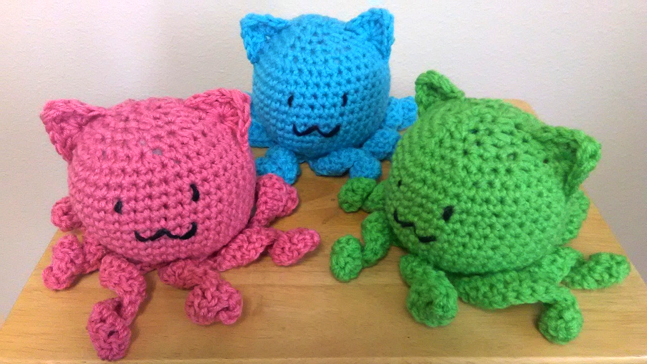 Crocheted Catopuss, three large ones, in pink, blue, and green.